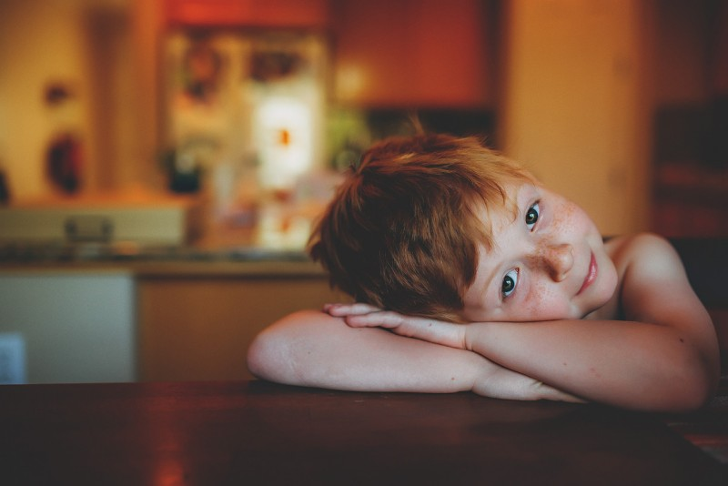 photo of young freckles red hair boy arms crossed on table looking at camera by Winnie Bruce