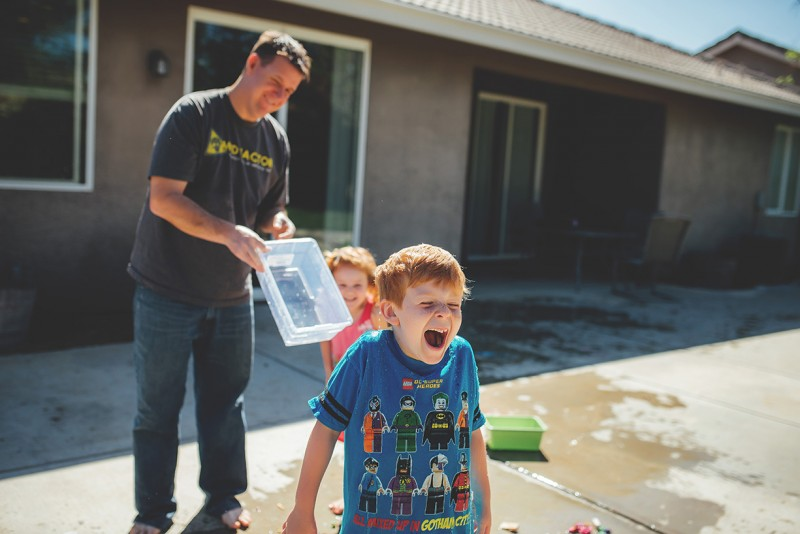 photo of father pouring water on young son back in driveway by winnie bruce