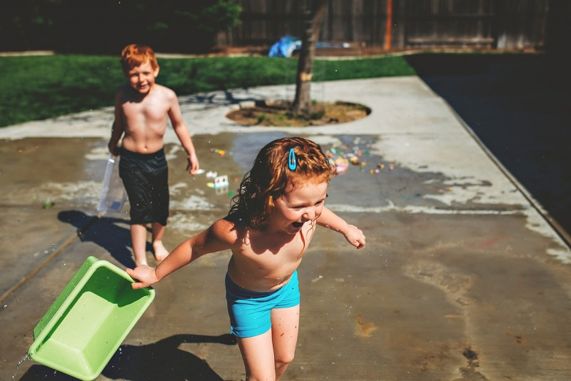 photo of two young red headed siblings water fight in driveway by winnie bruce