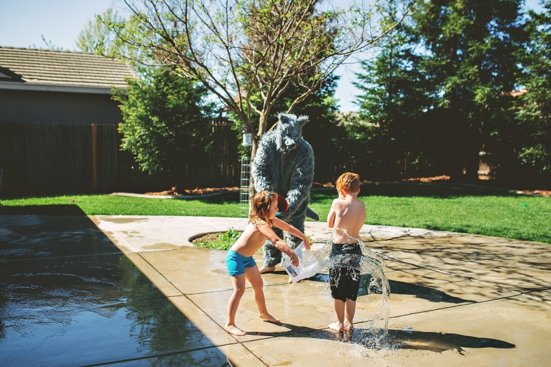 photo of man in wolf suit spraying two young children with hose in driveway by winnie bruce
