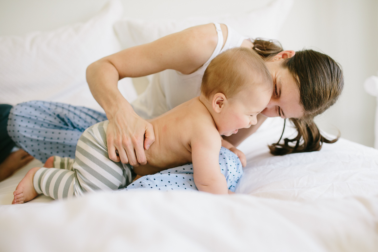 a close up picture of a mother playing with her baby son on her bed by chicago photographer Katie Kett