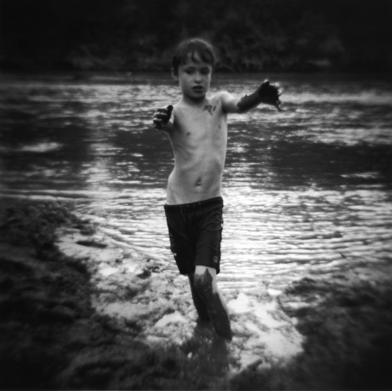 black and white image of boy at river with mud on his hands by photographer jennifer shaw