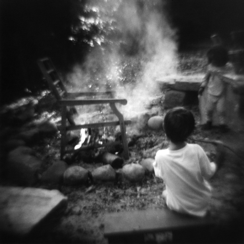 black and white image of chair burning in fire with little kids watching by photographer jennifer shaw