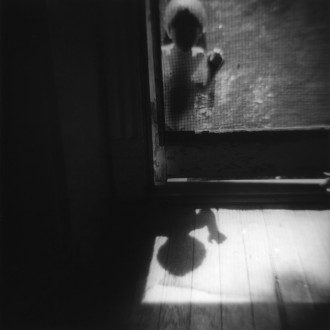 black and white photo of boy outside screen door in new orleans by photographer jennifer shaw
