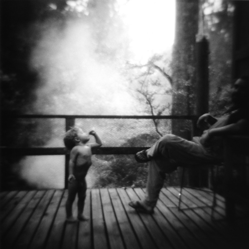black and white photograph of little boy on porch with adult by photographer jennifer shaw