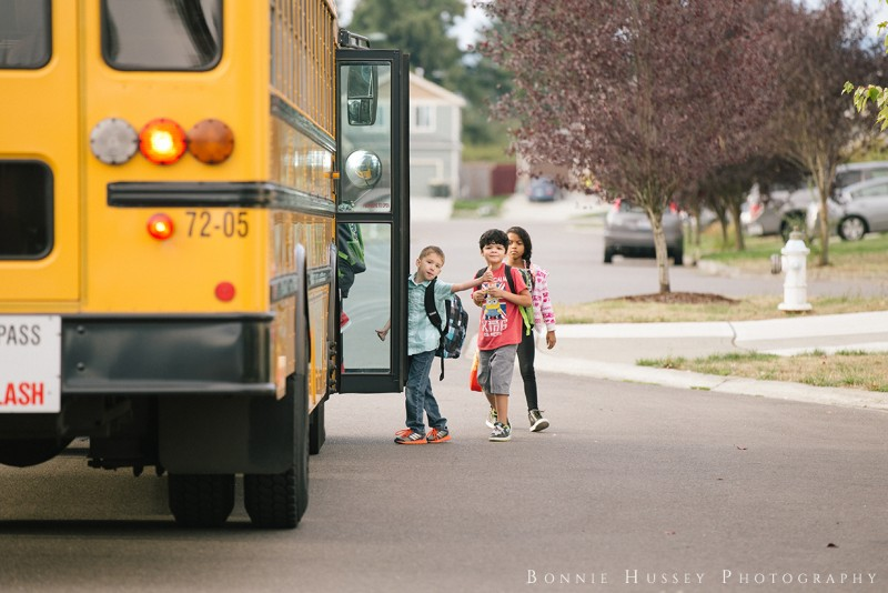 image of boy giving thumbs up as he gets on school bus by Bonnie Hussey