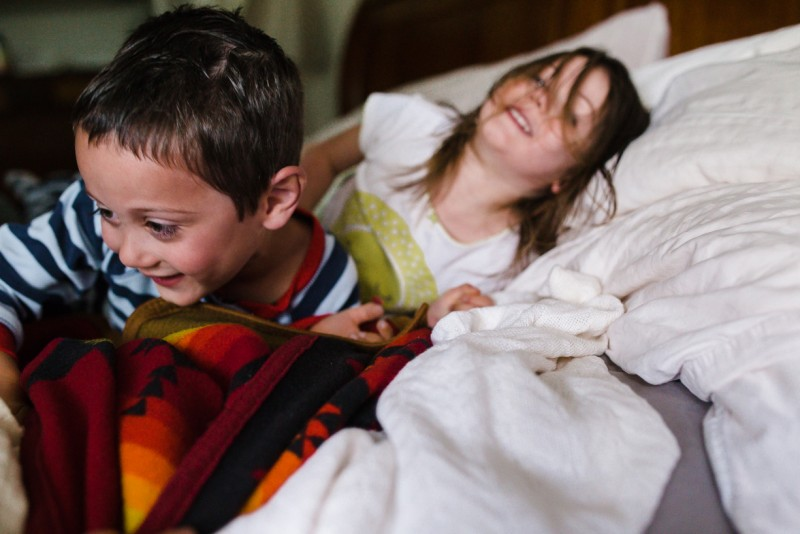image of two young kids playing on bed in pajamas by kari wattenbarger