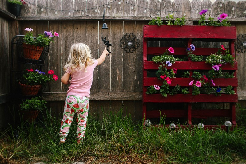 photo of a young girl in pajamas in yard touching chime by Rebecca Wang