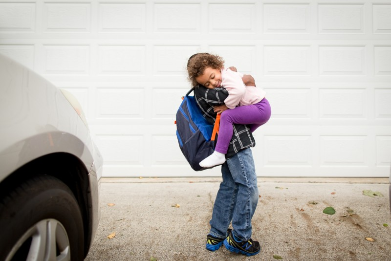 photo of big brother giving little sister a hug before school by jennifer bogle