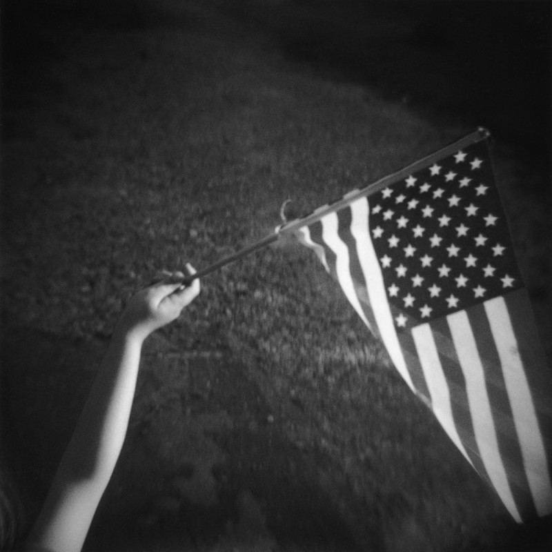 photo of child waving an american flag in black and white by photographer jennifer shaw
