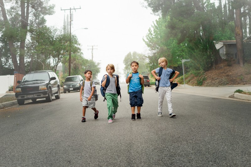 photo of four young boys walking in street to school by erica montgomery