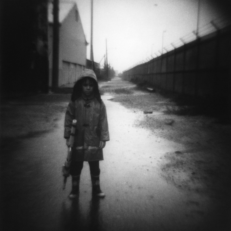 photo of little boy in raincoat holding nerf gun by photographer jennifer shaw