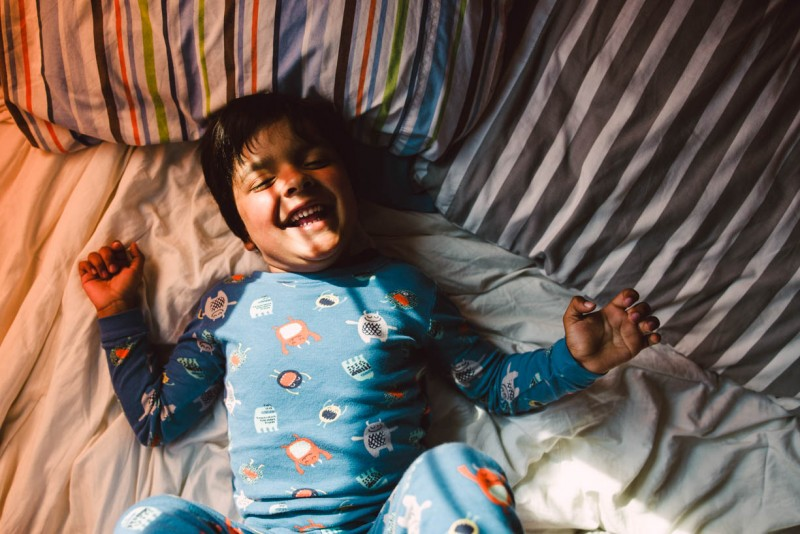 photo of young boy laughing on bed in monster pajamas by antonieta Esis