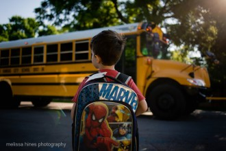 picture of a young boy superman backpack looking at school bus by melissa hines