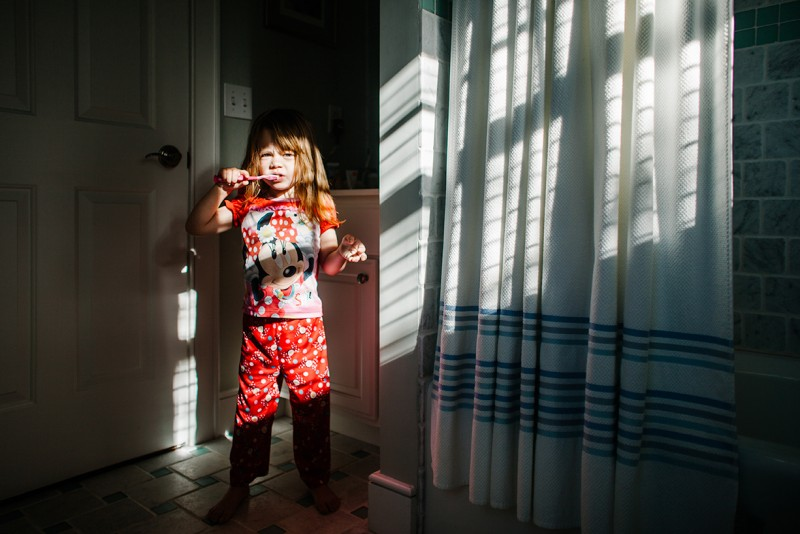 picture of a young girl in pajamas brushing her teeth by Lauren Mitchell