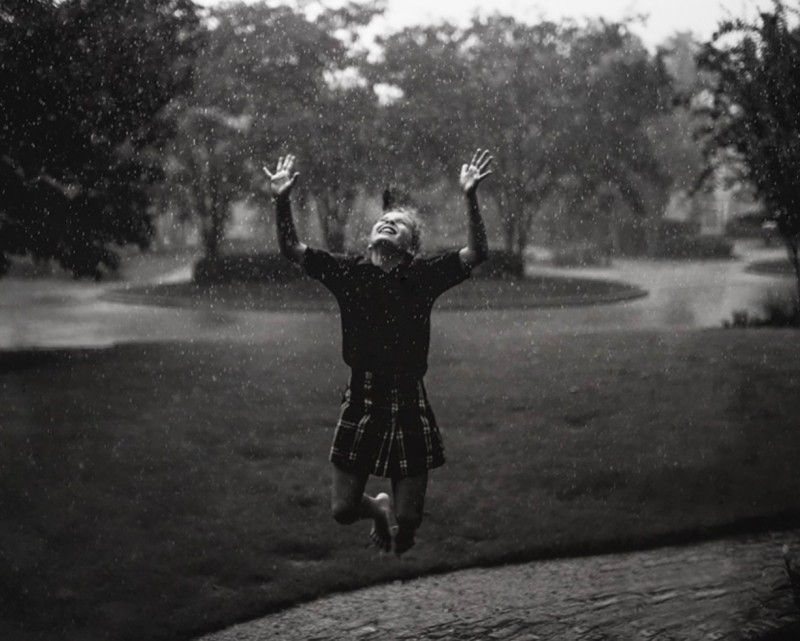 picture of girl in school uniform jumping joy in rain by kate t parker