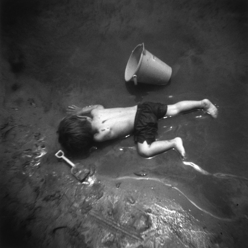 picture of little boy laying down in mud with pail and shovel by photographer jennifer shaw