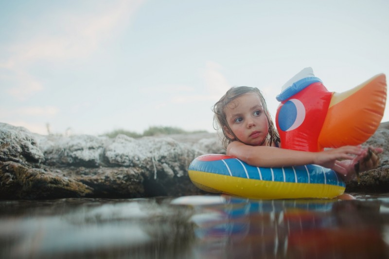 Young-child-in-swimming-float-in-water-by-Summer-Murdock