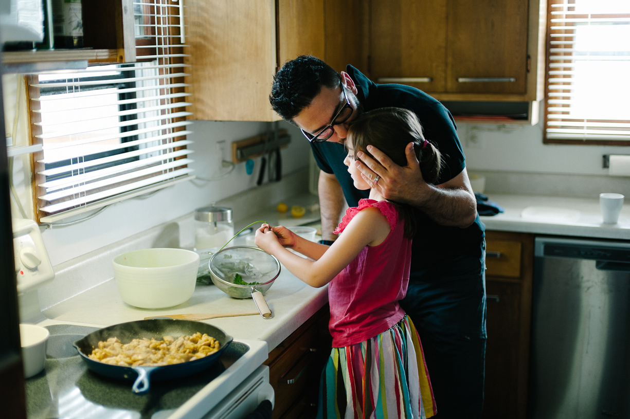 photo of young girl making breakfast in kissed father kissing daughter by Ryan Stadler