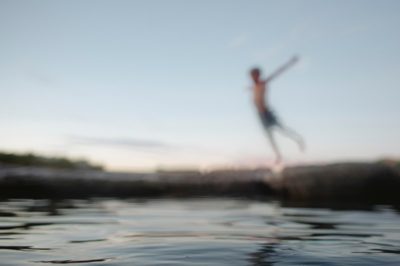 out-of-focus-image-of-boy-jumping-into-Utah-swimming-hole-by-Summer-Murdock