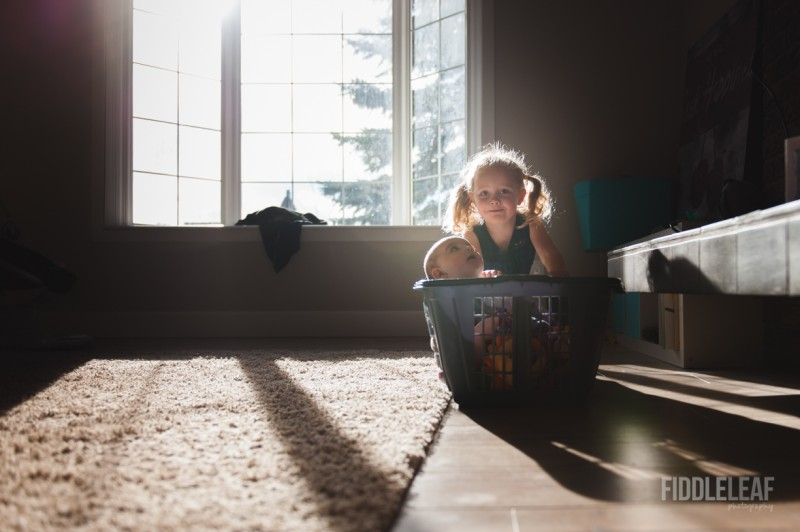 pictures of sisters playing with laundry basket inside by window by Kelly Marleau