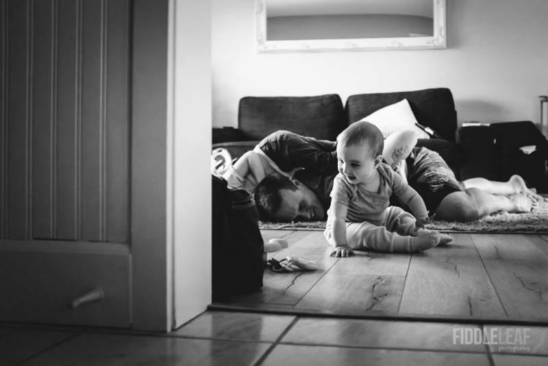 image of father and small children wrestling on floor black and white by Kelly Marleau
