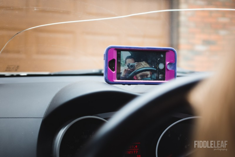 photo of mother taking picture of self and daughter steering wheel smartphone reflection cracked windshield by kelly marleau