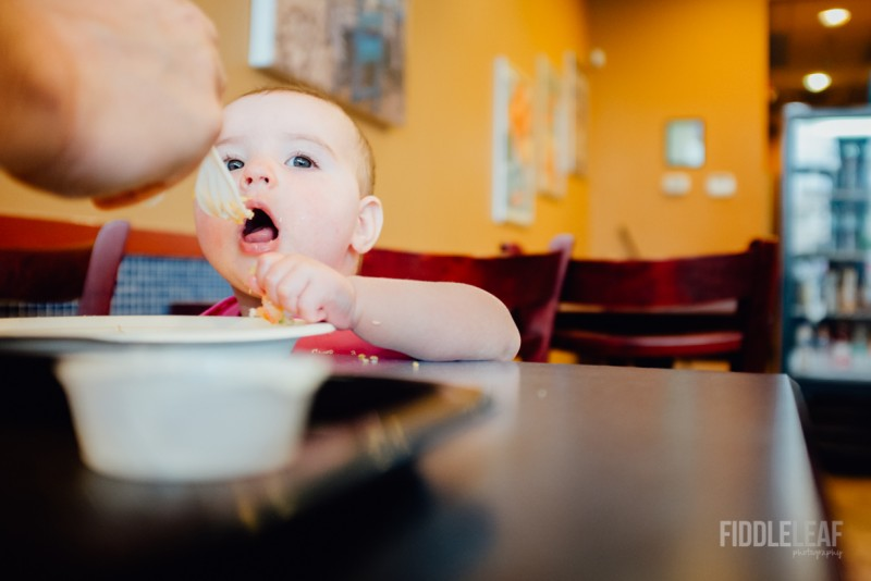 picture of baby being fed by fork in restaurant by Kelly Marleau