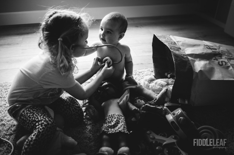 picture of older sister listening to little sister hearbeat with stethoscope black and white by Kelly Marleau