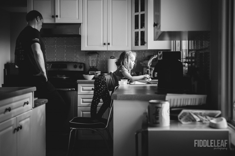 image of young girl standing on chair to reach kitchen sink father cooking by Kelly Marleau