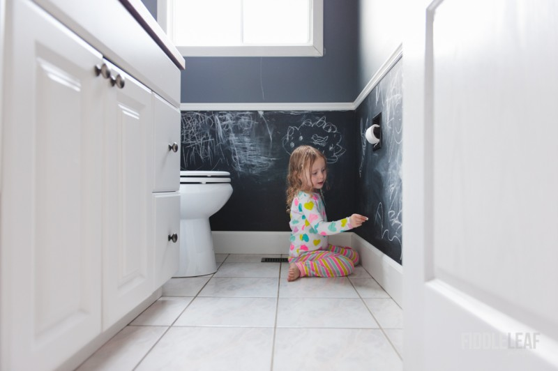 photo of young girl drawing on chalkboard walls in bathroom by Kelly Marleau