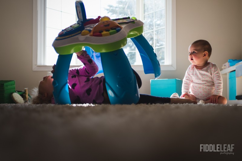 photo of toddler under toy sister watching by Kelly Marleau