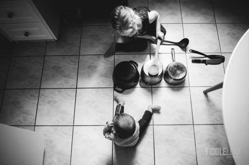 image of young kids playing with pans on kitchen floor from above black and white by Kelly Marleau
