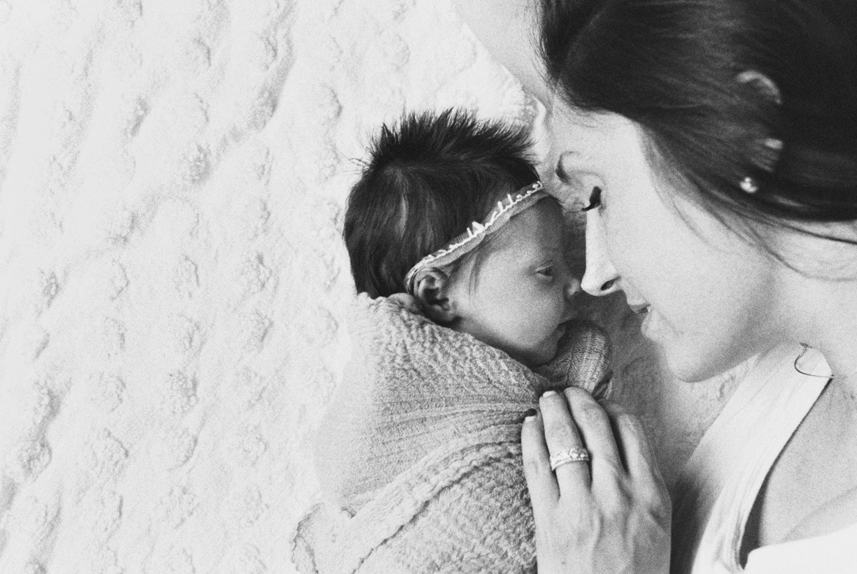a black and white film photo of a mom snuggling her newborn by portland oregon photographer marla cyree
