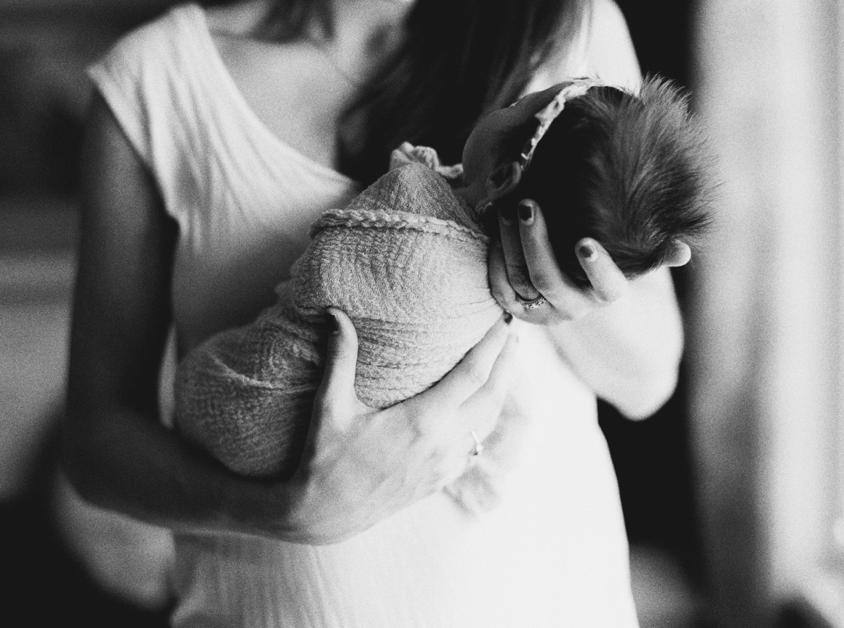 a black and white photo of a mother cradling her newborn by Portland Oregon photographer Marla Cyree