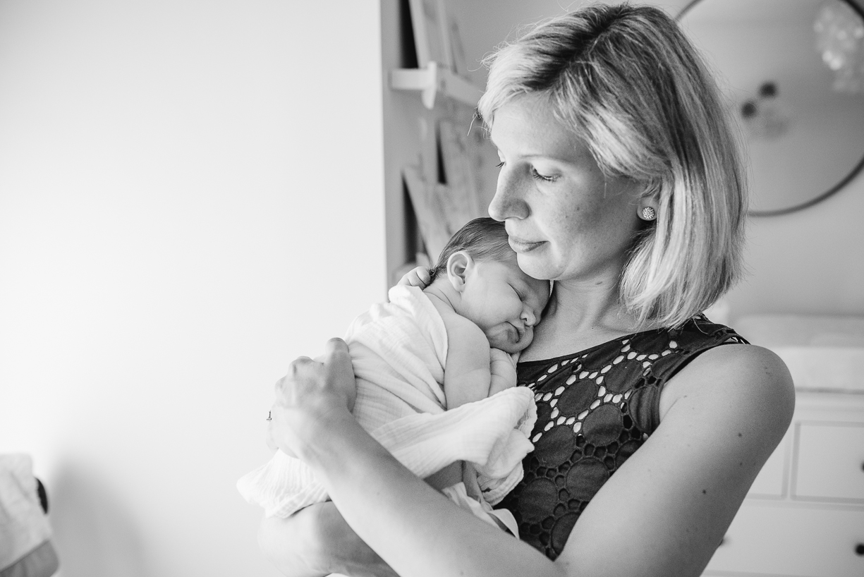 a black and white photograph of a mom with her newborn baby by boston photographer laura leibowitz