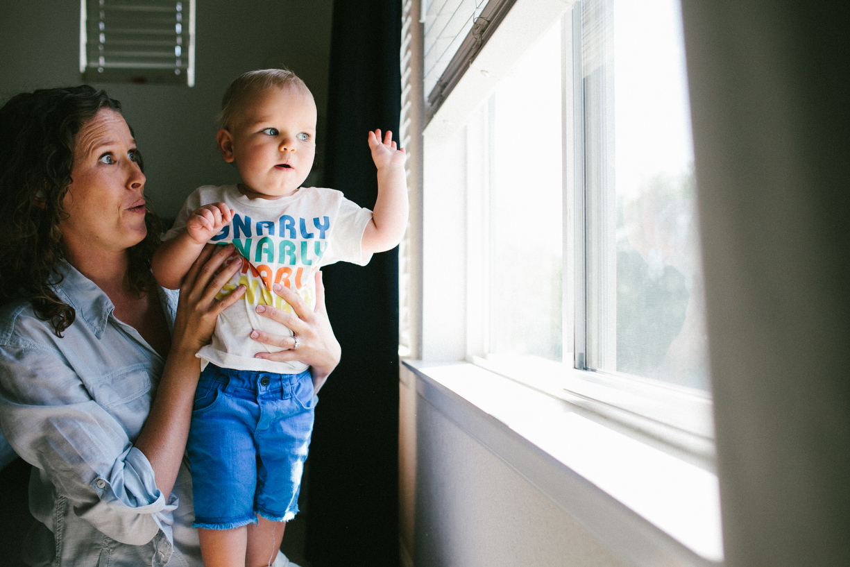 a mother holds up her toddler son in a picture by kansas city missouri photographer ashley parsons