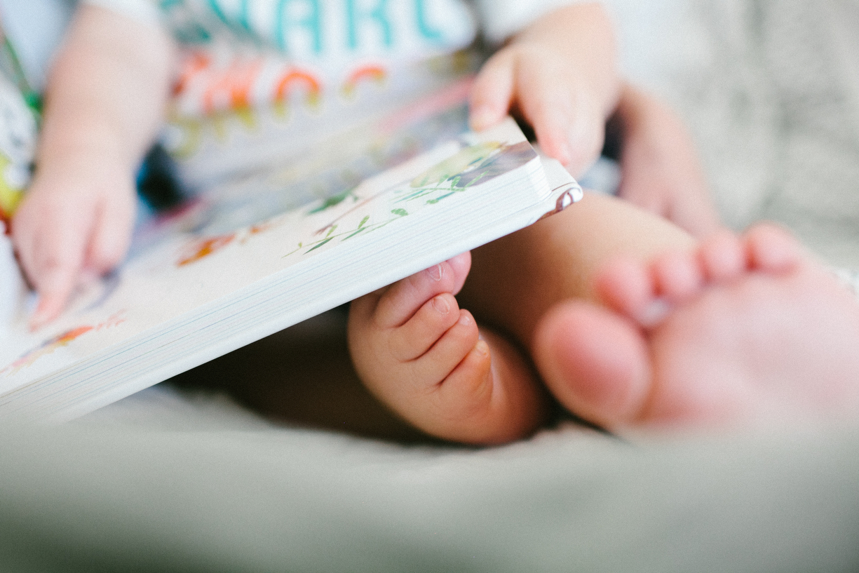 a photo of a baby's feet as he reads with his mom by kansas city photographer ashley parsons