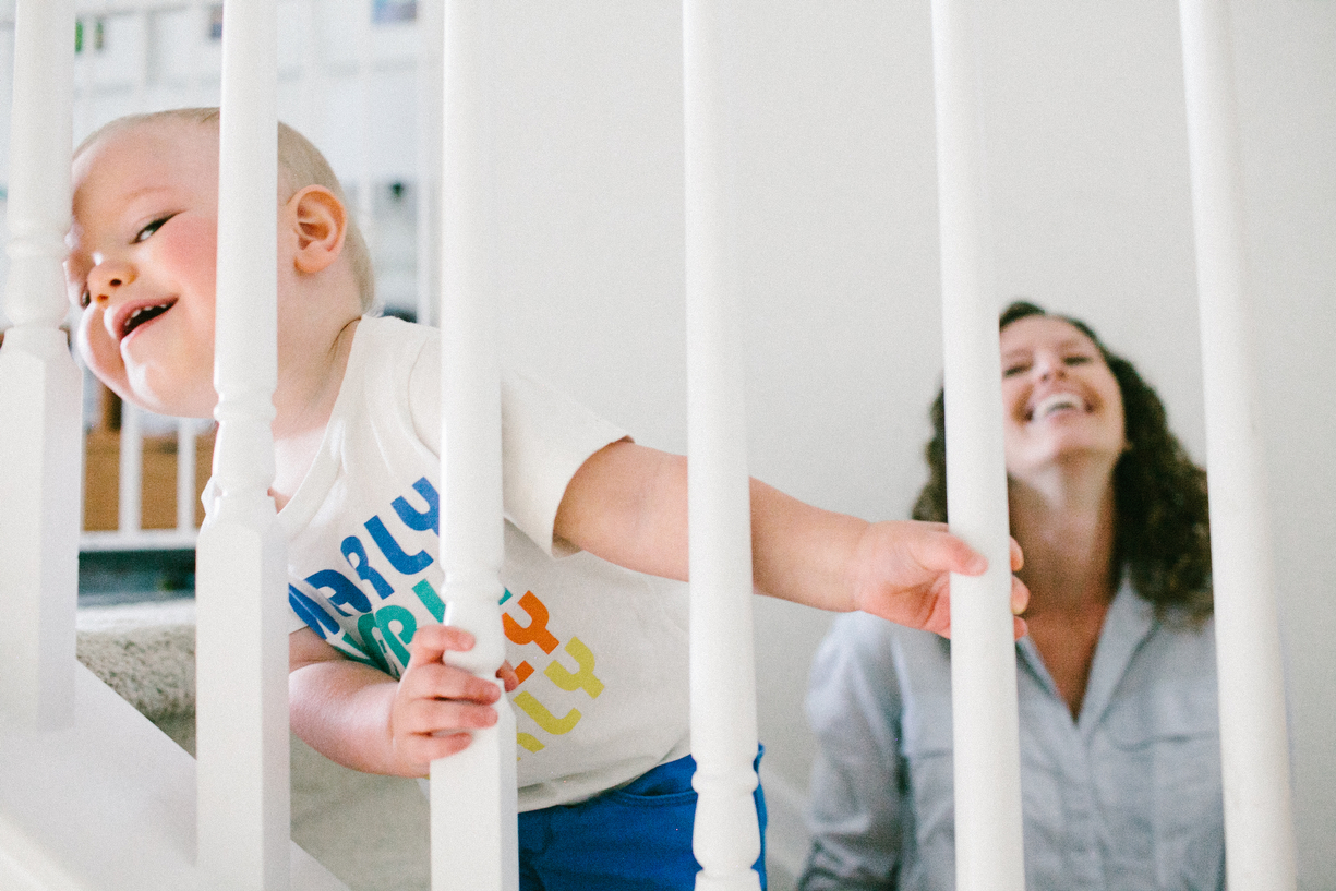 a photo of a child and his mom laughing on the stairs by kansas city photographer ashley parsons