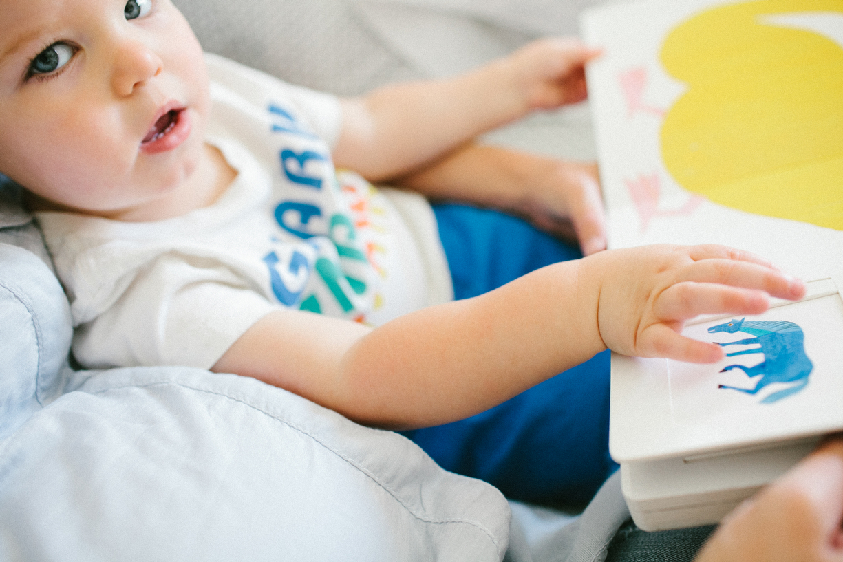 a photo of a child looking up from reading his book by kansas city photographer we are the parsons