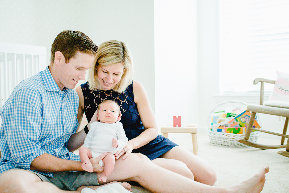 a photo of a family snuggling their newborn baby by boston photographer laura leibowitz