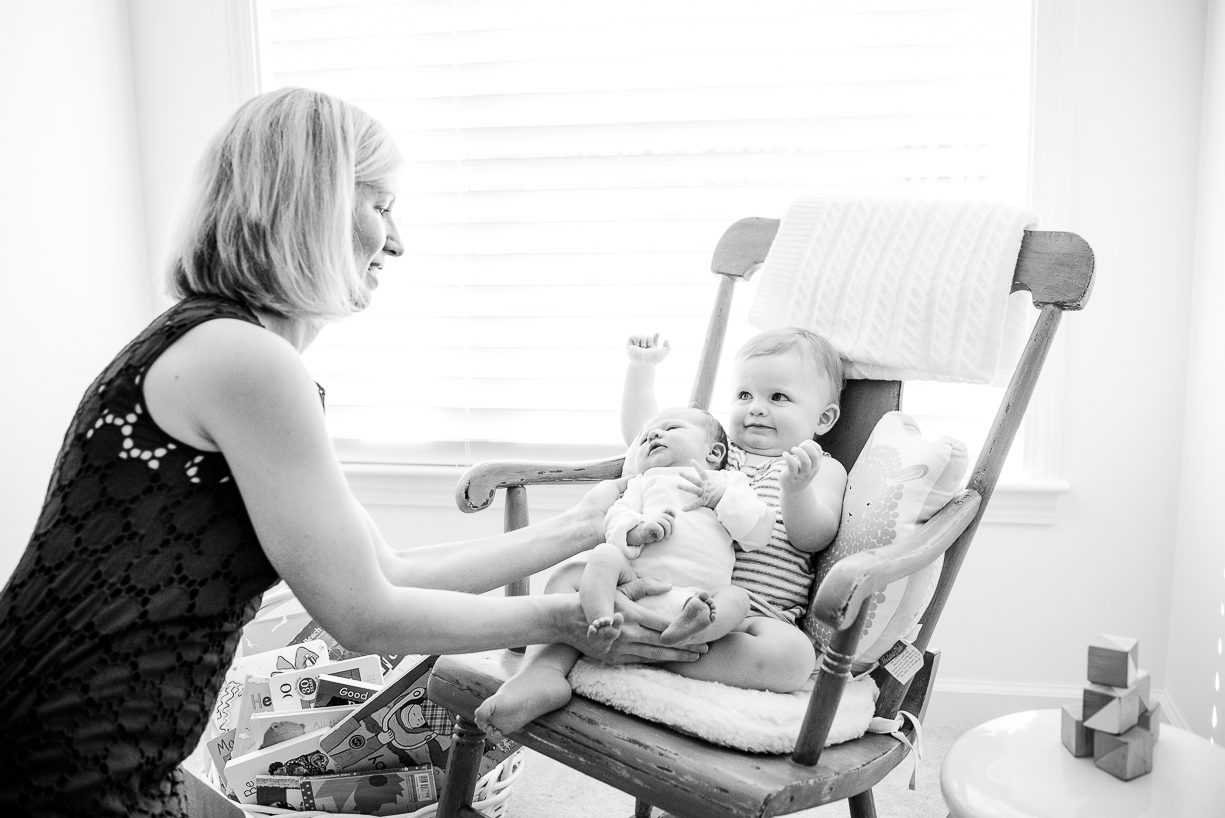 a photo of a mom with her infant and toddler daughters by boston area photographer Laura Leibowitz