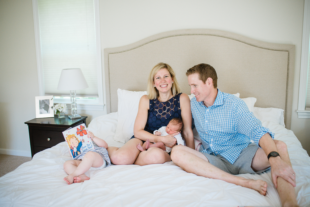 a photo of a new family snuggling on the bed with their newborn by boston photographer laura leibowitz