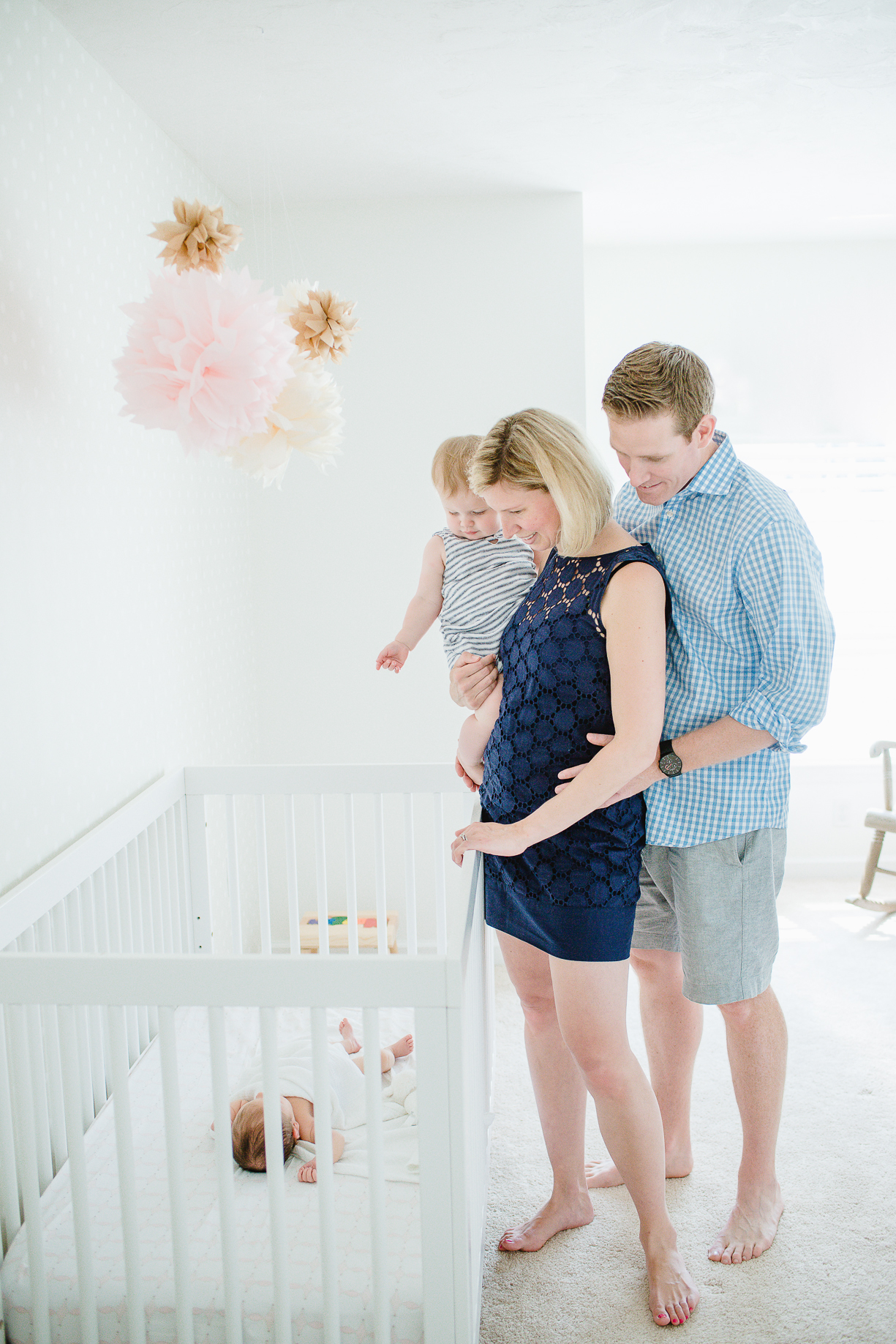 a picture of a family with their newborn baby in the nursery by Boston photographer Laura Leibowitz
