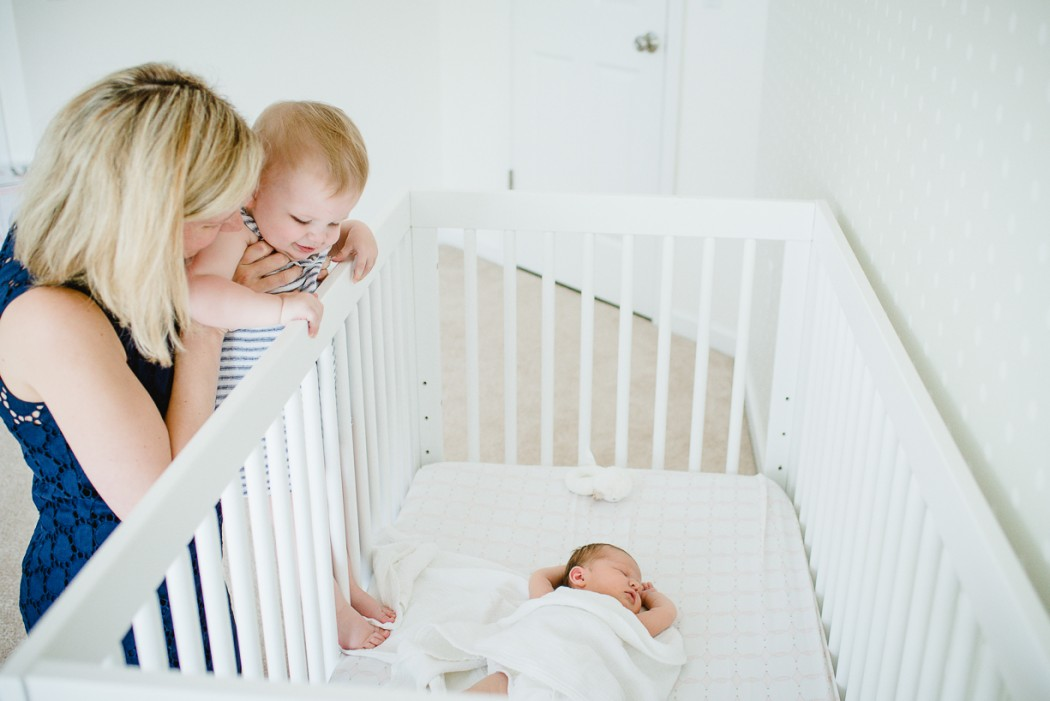 a picture of a mom holding up her daughter to look at her newborn sister laying in the crib by boston photographer laura leibowitz