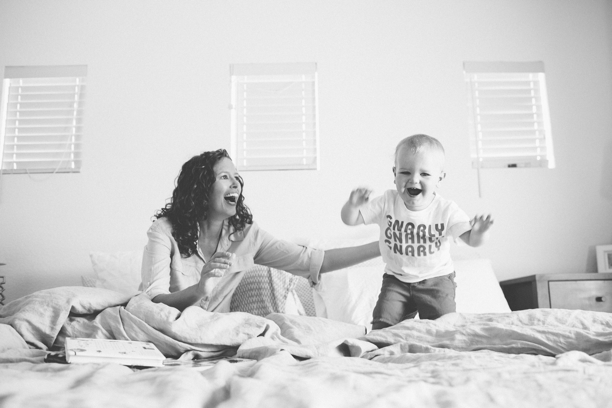 a picture of a mother watching her son jump on the bed by photographer ashley parsons