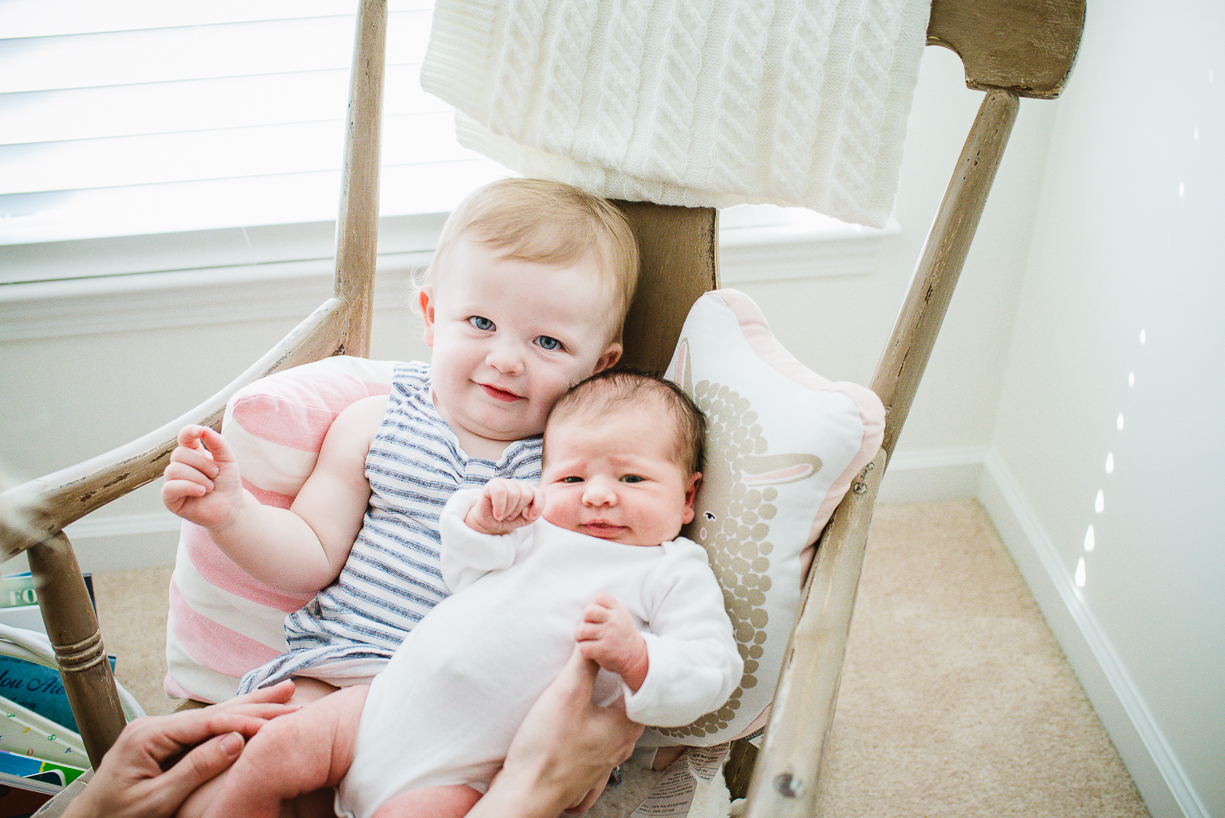 a picture of a toddler big sister with her newborn sibling by boston photographer laura leibowitz
