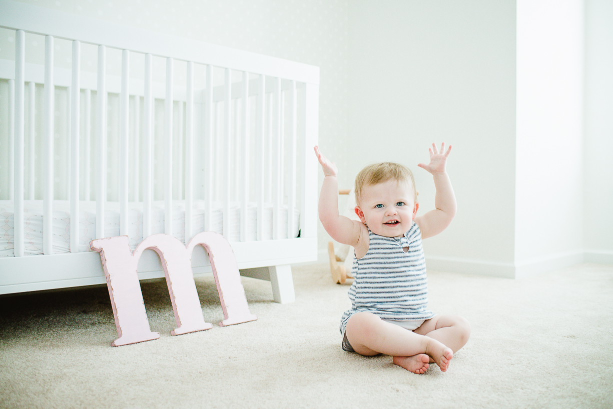 a picture of a toddler with her arms up in the air by boston photographer laura leibowitz