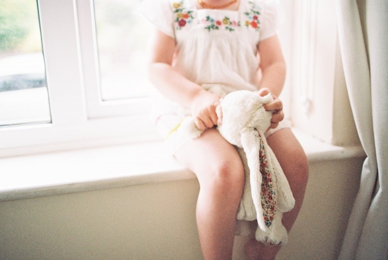 little girl in cute white dress on windowsill holding her lovey pic by photographer kjrsten madsen