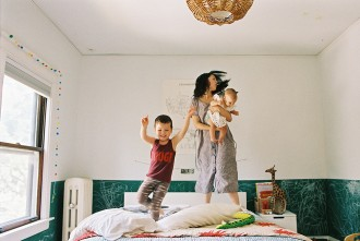 mom and kids jumping on the bed photo by photographer suzy brown